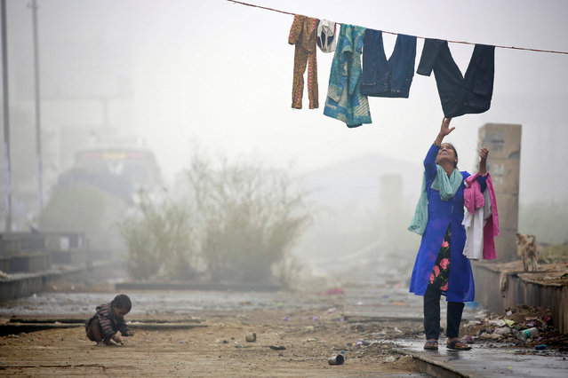 A woman collects her washing during heavy fog in Delhi, India December 1, 2016. (Photo by Cathal McNaughton/Reuters)