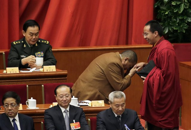 Tudeng Kezhu, a Tibetan delegate, touches the hand of Gyaltsen Norbu, the 11th Panchen Lama and a delegate, with his forehead during the opening session of the Chinese People's Political Consultative Conference (CPPCC) at the Great Hall of the People in Beijing, March 3, 2015. REUTERS/Jason Lee
