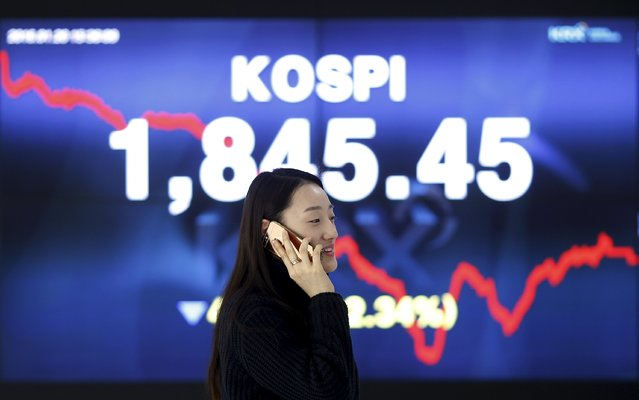A woman talking on the phone walks past an electronic board of the Korea Composite Stock Price Index (KOSPI) at the Korea Exchange (KRX) in Seoul, South Korea, January 20, 2016. (Photo by Kim Hong-Ji/Reuters)