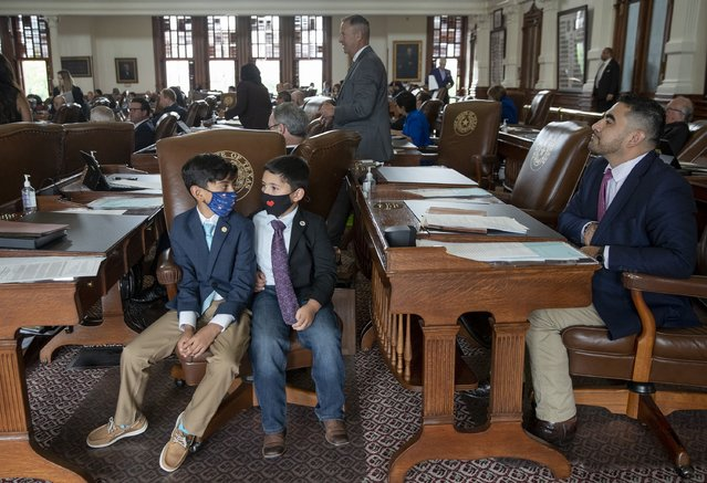 Armando Walle, 10, left, and his brother Joaquin Walle accompany their father state Rep. Armando Walle, D- Houston, right, on the House floor at the Capitol on the next-to-last day of the 87th Texas Legislature on Sunday May 30, 2021. (Photo by Jay Janner/Austin American-Statesman via AP Photo)