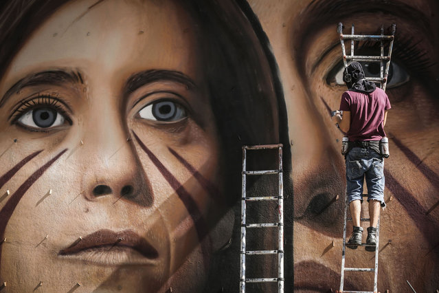Street artist Jorit works on the mural depicting Ilaria Cucchi in the Arenella district, Naples, Italy on 12 October 2018. Dozens of passersby photograph him and bring him support, food and drink. (Photo by Roberta Basile/IPA/Rex Features/Shutterstock)