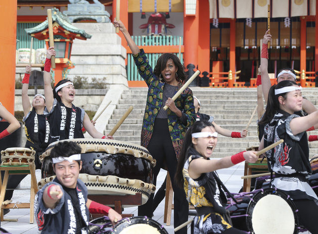 U.S. first lady Michelle Obama plays the taiko drum with the Akutagawa High School Taiko Club members during her visit to Fushimi Inari Shinto Shrine in Kyoto in western Japan Friday, March 20, 2015. (Photo by Koji Sasahara/AP Photo)