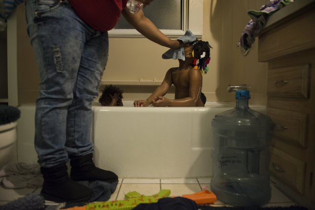Nakeyja Cade bathes her three children in boiled bottled water after her one-year-old daughter Zariyah Cade (center left) had a blood test scoring high in lead content in Flint, MI on March 1, 2016. The working single mother of three says Zariyah started having seizures months after she was born and believes that the lead in the water is responsible.  Her 3-yr-old son was tested and his levels are not as high.  She has yet to test her 50year-old daughter and herself.   After trying three different water filters, water in the house is testing high for lead.  The City of Flint, through a series of maneuvers, went from using drinking water from Detroit to water from the Flint river. The Flint river water has now been shown to contain trihalomethanes, a chlorine byproduct linked to cancer and other diseases.  A study by the Hurley Medical Center stated the proportion of infants and children had an extremely above-average levels of lead in their blood which had nearly doubled since the city switched its water source.  (Photo by Linda Davidson/The Washington Post)