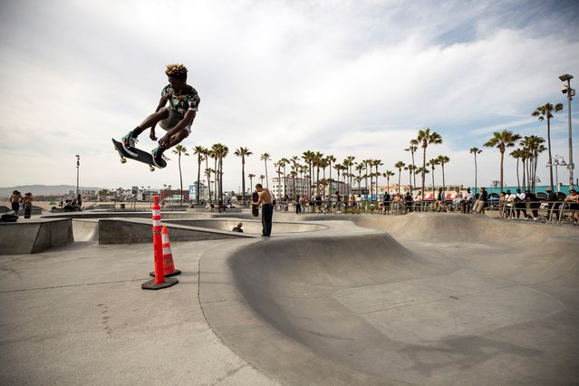 Skaters borders perform in front of a crowd without wearing face masks as California drops most of its restrictions put in place in response to the COVID-19 pandemic, in Venice Beach, California, USA, 15 June 2021. (Photo by Etienne Laurent/EPA/EFE)