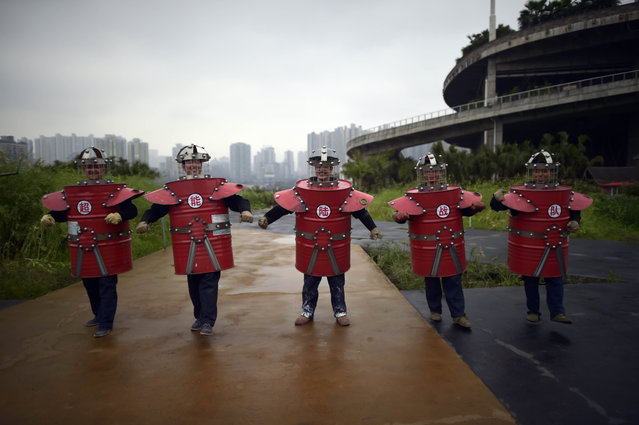 In this Thursday, March 19, 2015 photo, workers in outfits made from scrap material parade through a farm on the rooftop of a door manufacturer in Chongqing municipality in southwest China. (Photo by AP Photo)