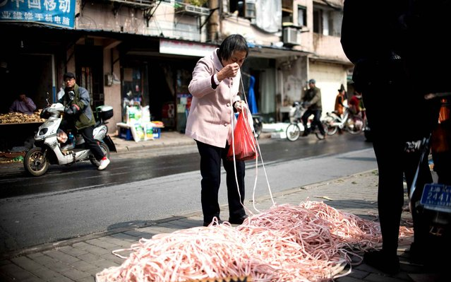 An elderly woman buys elastic bands at a market in Shanghai on March 17, 2015. (Photo by Johannes Eisele/AFP Photo)