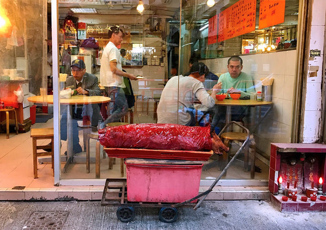 CHINA: Customers eat at a restaurant as a cooked pig sits on a cart on the street outside in Hong Kong, China, December 12, 2016. (Photo by David Gray/Reuters)