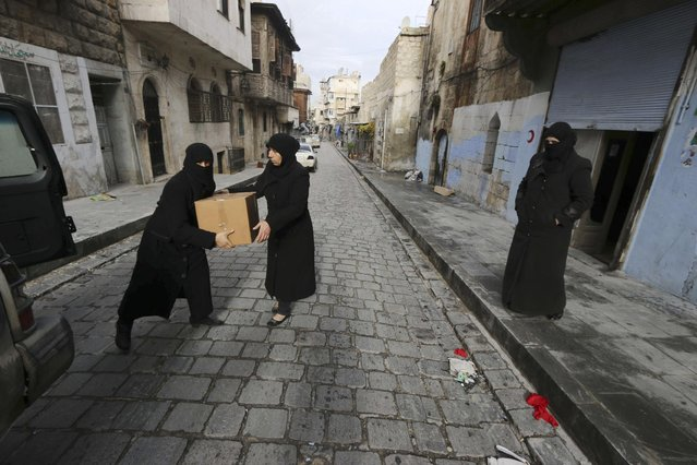 Umm Mohamad (L), a masters graduate and commander of the all-female Mother Aisha battalion, hands a box of medical supplies to a fellow member of the battalion near a field hospital in Aleppo January 3, 2015. The Mother Aisha battalion, controlled by the Free Syrian Army, provides aid and security in addition to being a full military unit. The women who make up this force not only operate as fighters on the Old Aleppo frontline, but are also in charge of two field hospitals for injured fighters and a police station for women detainees. (Photo by Abdalrhman Ismail/Reuters)