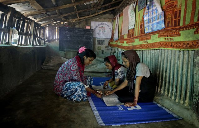 In this August 22, 2018, photo, Rahima Akter, left, teaches her siblings inside the family hut in Kutupalong refugee camp, in Bangladesh. Rahima is a 19-year-old refugee who dreams of becoming the most educated Rohingya woman in the world. While she is mostly busy preparing university applications, Rahima spends her spare time going door-to-door at the expansive camps, documenting first-person accounts of people who fled Myanmar last year. (Photo by Altaf Qadri/AP Photo)