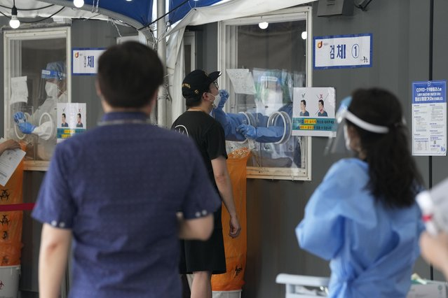 A medical worker in a booth takes a nasal sample from a man during a coronavirus testing at a makeshift testing site in Seoul, South Korea, Friday, July 16, 2021. South Korean officials are pushing for tightened pandemic restrictions beyond the hard-hit capital area as they wrestle with a record-breaking surge in coronavirus cases. (Photo by Ahn Young-joon/AP Photo)