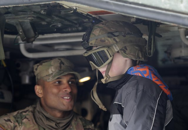 A US army soldier shows the inside of a stryker armored vehicle to a kid during a stop of his convoy in Prague, Czech Republic, Tuesday, March 31, 2015. (Photo by Petr David Josek/AP Photo)