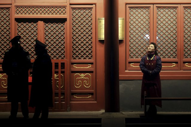A temple staff and security guards wait before Yonghegong Lama Temple opens its doors for people to burn incense and pray for good fortune on the first day of the Lunar New Year of the Monkey in Beijing, China, February 8, 2016. (Photo by Damir Sagolj/Reuters)