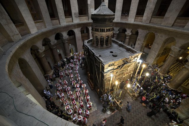 Roman Catholic clergymen carry palm fronds during the Palm Sunday procession at Church of the Holy Sepulchre, traditionally believed by many to be the site of the crucifixion and burial of Jesus Christ, in Jerusalem's Old City, Sunday, March 29, 2015. Palm Sunday marks for Christians Jesus Christ's entrance into Jerusalem when his followers laid palm branches in his path, prior to his crucifixion. (Photo by Oded Balilty/AP Photo)