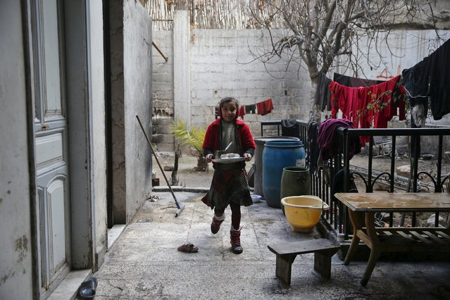 Hadeel, 10, daughter of Shahrour, walks with a coffee tray at her home in the besieged town of Arbeen, in the Damascus suburbs, Syria February 6, 2016. (Photo by Bassam Khabieh/Reuters)