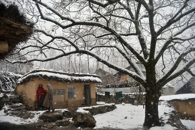 A Kashmiri muslim family stand outside their mud house during snowfall on the outskirts of Srinagar on January 5, 2017. (Photo by Tauseef Mustafa/AFP Photo)