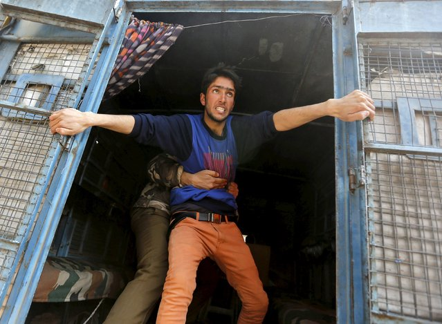 A supporter of Kashmiri lawmaker Sheikh Abdul Rashid, also known as Engineer Rashid, attempts to jump from a police vehicle after he was detained by Indian police during a protest in Srinagar February 17, 2016. Dozens of supporters of Rashid were detained by police on Wednesday during a protest against the arrest of former Delhi University lecturer (SAR) Syed Abdul Rehman Geelani and also against the deaths of two youths in south Kashmir's Pulwama district, protesters said. (Photo by Danish Ismail/Reuters)