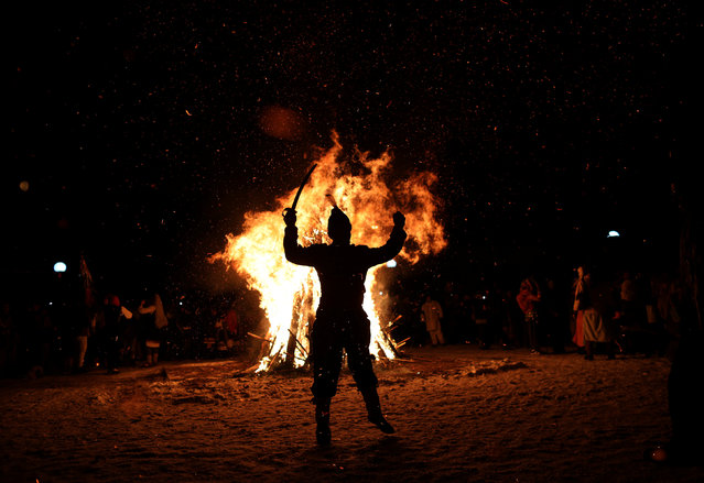"""A man dressed in a costume made of animal fur, called """"kuker"""", dances around a bonfire during a festival in the town of Batanovtsi, Bulgaria January 13, 2017. (Photo by Stoyan Nenov/Reuters)"""