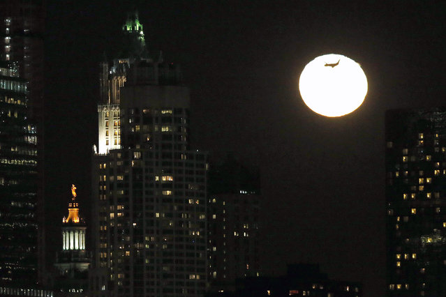 An airplane flies past the rising moon in its waning gibbous stage as viewed from Jersey City, N.J., Thursday, February 5, 2015. The statue known as Civic Fame, bottom left, which stands atop of the Manhattan Municipal Building in New York, is also visible. (Photo by Julio Cortez/AP Photo)