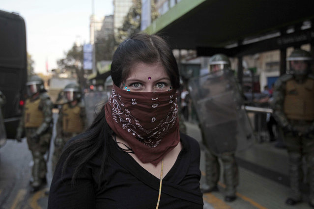 A woman has her picture taken in front of a group of police officers during a demonstration in Santiago, Chile, Thursday, April 16, 2015. (Photo by Luis Hidalgo/AP Photo)