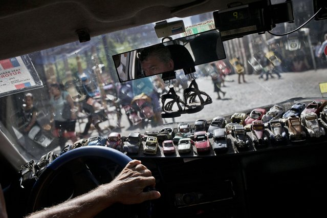 Miniature cars cover the dashboard of taxi driver Roman Donoso as he navigates the streets of downtown Santiago, Chile, Monday, February 22, 2016. Donoso said he has just 40 miniature cars inside his taxi, with hundreds more at home. (Photo by Esteban Felix/AP Photo)