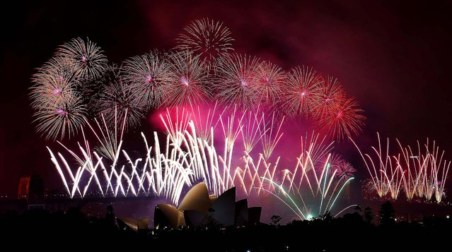Fireworks explode over the Harbour Bridge and the Opera House during New Year's Eve celebrations in Sydney, Australia. (Photo by Rob Griffith/Associated Press)