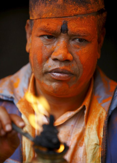 """A devotee smeared in vermillion powder lights a """"Chirag"""", traditional lamp, while celebrating the Sindoor Jatra vermillion powder festival at Thimi, in Bhaktapur April 15, 2015. (Photo by Navesh Chitrakar/Reuters)"""