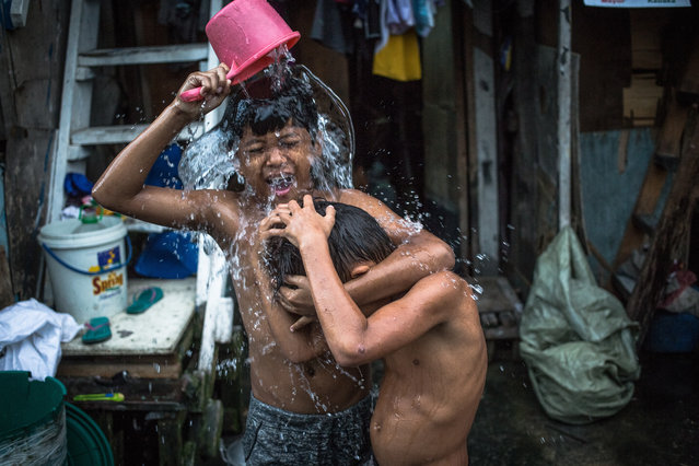 Children living in a slum area take a bath, in Manila, Philippines, 01 December 2018. A slum area is traditionally described as a settlement of improvised housing, also known as shanties, made of sheets of plastic, cardboard boxes, corrugated metal, and plywood. In many growing urban cities such as Manila, New Delhi, Cape Town, Jakarta or Caracas slums are the main types of housing for people with low-income. Slum areas are commonly lack of adequate living conditions, and residents of these areas often have no electricity, proper sanitation or clean water. One of eight people in our world live in slums. In total, around a billion people live in slum conditions today, according to the United Nations Human Settlements Programme (UN–Habitat). In the Philippines, according to a report by Homeless International, around 22.8 million of Filipinos reside in slums while the capital city of Manila has the highest homeless population of any city in the world at 3.1 million, out of which more than 70,000 are children. (Photo by Roman Pilipey/EPA/EFE)