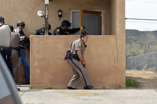In this photo provided by The Navajo Times, Navajo Nation Police go door-to-door searching a subdivision for a reported gunman in Ft. Defiance, Ariz., Friday, April 10, 2015. Navajo Nation police have arrested a man who they say fired shots in the northeastern Arizona housing complex. (Photo by Donovan Quintero/AP Photo/The Navajo Times)