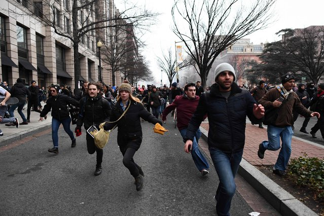 Anti- Trump protesters flee during clashes with police in Washington, DC, on January 20, 2107. Masked, black- clad protesters carrying anarchist flags smashed windows and scuffled with riot police Friday in downtown Washington, blocks away from the route of the parade in honor of newly sworn- in President Donald Trump. (Photo by Jewel Samad/AFP Photo)