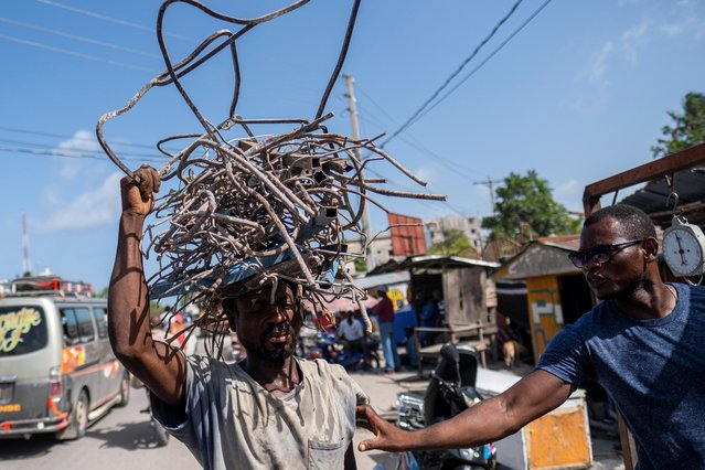A recycler offers to buy the metal from a man carrying on his head a pile of metal scavenged from houses destroyed by last week's quake in Les Cayes, Haiti on August 21, 2021. (Photo by Ricardo Arduengo/Reuters)