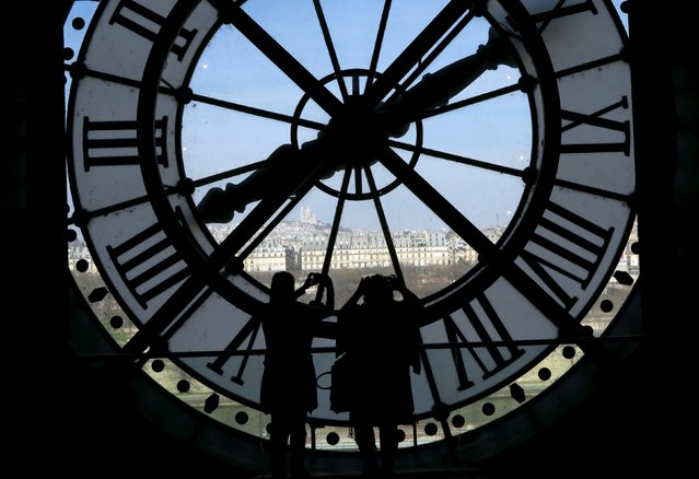 Visitors at the Musee d'Orsay are seen in silhouette as they take pictures from behind a giant clock face at the former Orsay railway station, with a view of the Sacre Coeur Basilica (rear), in Paris April 8, 2015. The national museum of the Musee d'Orsay opened in December 1986 and it displays collections of art from the period 1848 to 1914. (Photo by John Schults/Reuters)