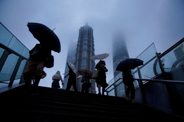 People hold umbrellas amid rainfall as Typhoon Chanthu approaches, in Shanghai, China on September 13, 2021. (Photo by Aly Song/Reuters)