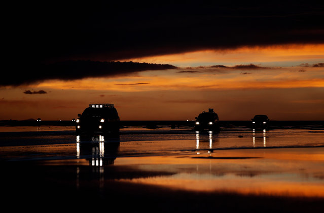 Cars leave as the sun sets over the Salar de Uyuni of Uyuni Salt Flat during Day 7 of the 2014 Dakar Rally on January 11, 2014 in Uyuni, Bolivia. (Photo by Dean Mouhtaropoulos/Getty Images)