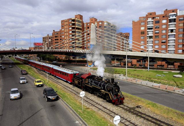 "A ""La Sabana"" tourist train steam locomotive manufactured in 1934 passes a central street in Bogota, March 8, 2015. (Photo by Jose Miguel Gomez/Reuters)"