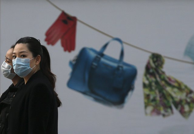 Women wearing masks walk past an advertisement board of a shopping mall in a hazy day in Beijing April 10,  2015. China's annual consumer inflation in March was 1.4 percent, matching the previous month's pace and slightly higher than the 1.3 percent projected in a Reuters poll. (Photo by Kim Kyung-Hoon/Reuters)