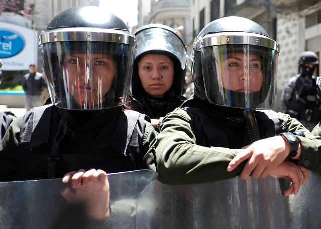 Riot policewomen stand guard next to vice presidency building during a rally on the Women's Day, in La Paz, Bolivia, March 8, 2019. (Photo by David Mercado/Reuters)