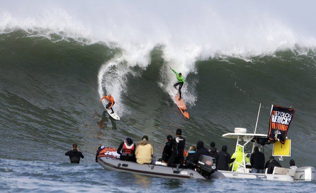 Shane Dorian, left, and Ben Wilkinson, right, catch a wave during the third heat of the first round of the Mavericks Invitational big wave surf contest Friday, January 24, 2014, in Half Moon Bay, Calif. (Photo by Eric Risberg/AP Photo)