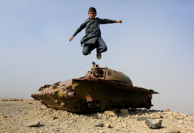 An Afghan boy jumps from the remains of a Soviet-era tank on the outskirts of Jalalabad, Afghanistan on February 15, 2019. (Photo by Reuters/Parwiz)