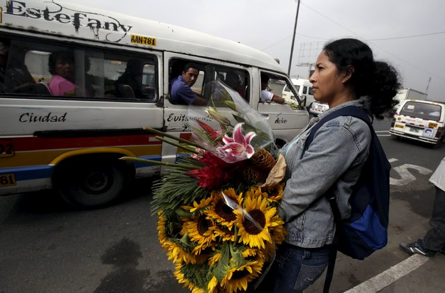 A woman carrying flowers waits for a bus outside the Piedra Liza flower market in Lima April 29, 2015. (Photo by Mariana Bazo/Reuters)