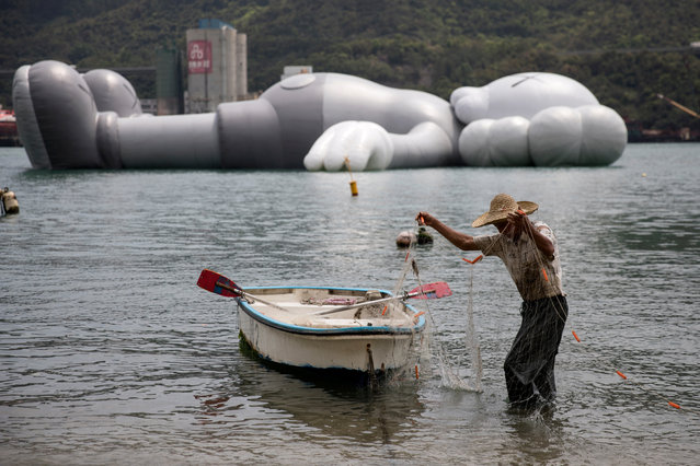 """A fisherman sorts his net next to the 37-meter-long """"KAWS:HOLIDAY Companion"""" inflatable sculpture in Tsing Yi, Hong Kong, China, 21 March 2019. KAWS:HOLIDAY, made by US artist and designer Brian Donnelly known professionally as Kaws, will be displayed in Hong Kong's Victoria Harbour from 22 to 31 March 2019. (Photo by Jerome Favre/EPA/EFE)"""
