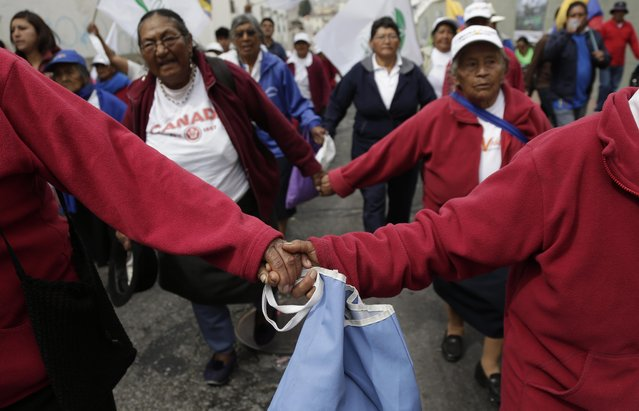 Women march hand in hand as they take part in the May Day parade, in Quito, Ecuador, Friday, May 1, 2015. Left-wing groups, governments and trade unions were staging rallies around the world Friday to mark International Workers Day, also known as May Day. (AP Photo/Dolores Ochoa)