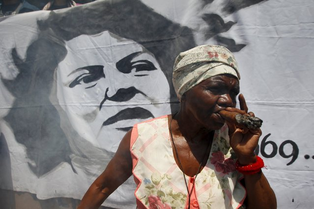 A Garifuna woman smokes a cigar in front of a banner depicting an image of slain environmental rights activist Berta Caceres during a protest to demand justice in Tegucigalpa, Honduras, March 17, 2016. (Photo by Jorge Cabrera/Reuters)
