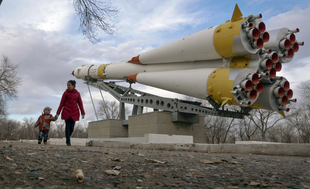 A woman walks with her child past a Soyuz rocket, installed as a monument at the Russian leased Baikonur cosmodrome, the world's first and largest operational space launch facility, in Baikonur, Kazakhstan, Saturday, November 12, 2016. The new Soyuz mission to the International Space Station (ISS) is scheduled for Friday, Nov. 18. (Photo by Dmitri Lovetsky/AP Photo)