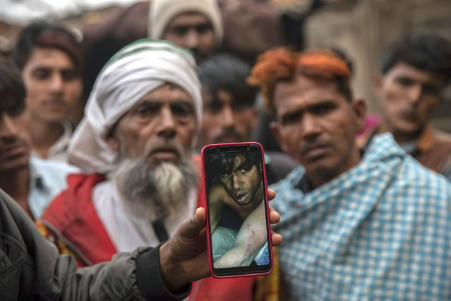 In this Tuesday, January 22, 2019 photo, a man holds a phone showing a video of Muslim farmer Saghir Khan, 25, moments after being beaten, Mirzapur, India. Most of the attacks by so-called cow vigilantes from Hindu groups have targeted Muslims, who make up 14 percent of India's 1.3 billion people. Hindus make up about 80 percent of the population. (Photo by Bernat Armangue/AP Photo)
