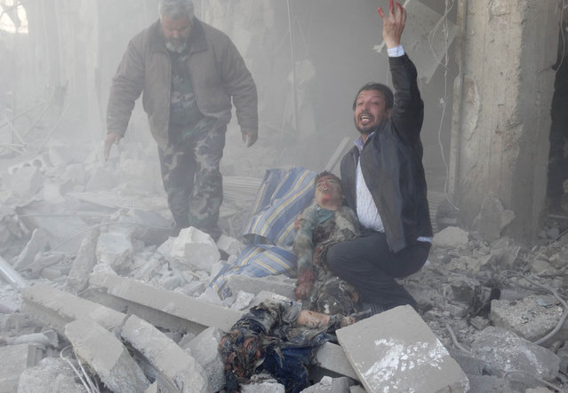 A Syrian man reacts as he carries the body of a child following a reported air strike by government forces on the al-Haidarya neighbourhood in the northern city of Aleppo on February 12, 2014. More than 136,000 people have been killed in Syria's nearly three-year war, and millions more forced to flee their homes. (Photo by Khaled Khatib/AFP Photo/Aleppo Media Centre)