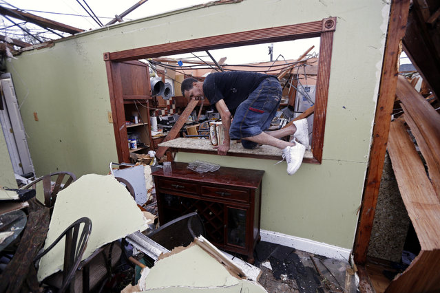 Gregory Rugon climbs out of his home after failing to find his glasses that he lost taking cover after a tornado hit his Warren Drive home, in the New Orleans East section of New Orleans, Tuesday, February 7, 2017. (Photo by Gerald Herbert/AP Photo)