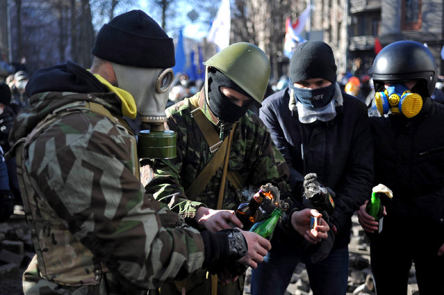 Anti-government protesters prepare Molotov cocktails during an anti-government protest in downtown Kiev, Ukraine, 18 February 2014. A least three protesters were killed in clashes with police on 18 February, Ukrainian opposition activists say. Violence erupted in the Ukrainian capital after anti-government protesters broke through a police cordon in front of parliament. (Photo by Alexey Furman/EPA)