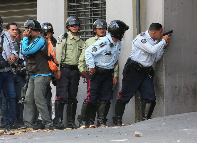 Pro-Juan Guaido military police officers confront Pro-Government armed civilians trying to protect themselves inside the Ministry of Housing at Avenida Francisco de Miranda on April 30, 2019 in Caracas, Venezuela. Through a live broadcast via social media, Venezuelan opposition leader Juan Guaido called for a military uprising against the government of Nicolás Maduro. He declared to be at the air base of La Carlota and was seen surrounded by soldiers and opposition activist Leopoldo Lopez, who was under house arrest. (Photo by Edilzon Gamez/Getty Images)