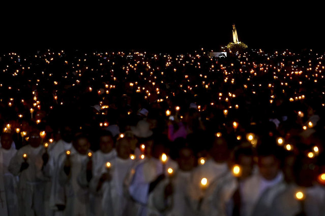 The image of Our Lady is transported among the faithfull in the Candles Procession during the annual 13th May pilgrimage to Fatima Sanctuary, Fatima, Portugal, 12 May 2015. (Photo by Paulo Novais/EPA)