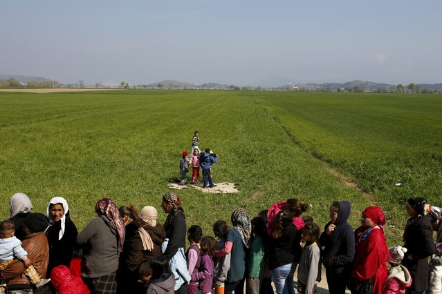 Migrants and refugees queue to receive food at a makeshift camp at the Greek-Macedonian border near the village of Idomeni, Greece, March 28, 2016. (Photo by Marko Djurica/Reuters)